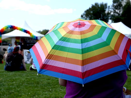 A spectator uses a rainbow umbrella as a sun shade at Capitol Pride at Riverfront Park in Salem on Saturday, Aug. 15, 2015.