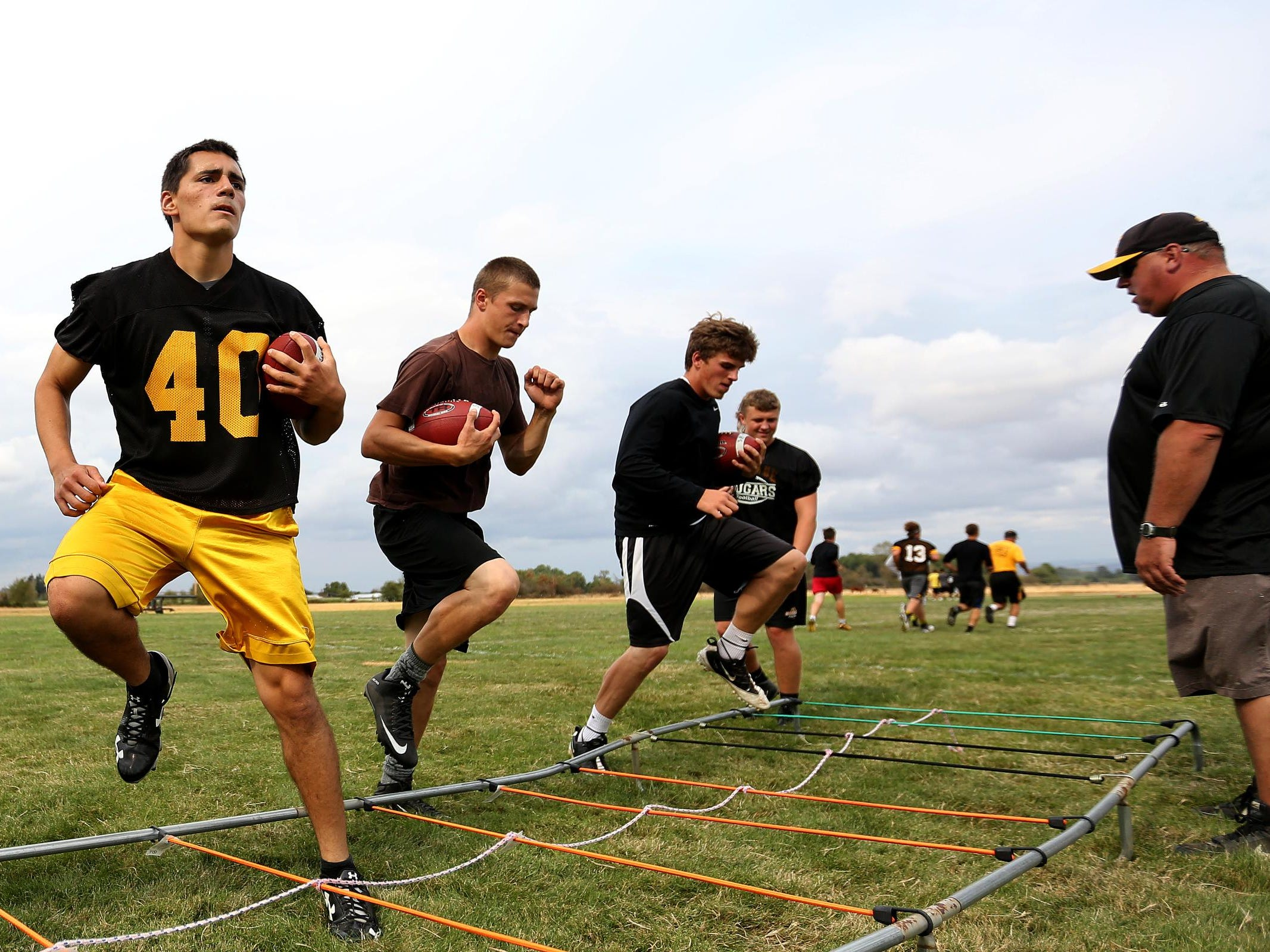 Malachi Gonzalez, left, a senior full back and line backer, runs drills during football practice at Cascade High School in Turner, Ore., on Friday, Aug. 14, 2015.