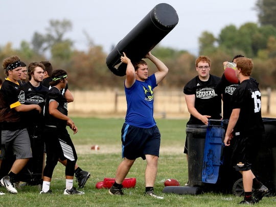 Players move equipment during football practice at Cascade High School in Turner, Ore., on Friday, Aug. 14, 2015.