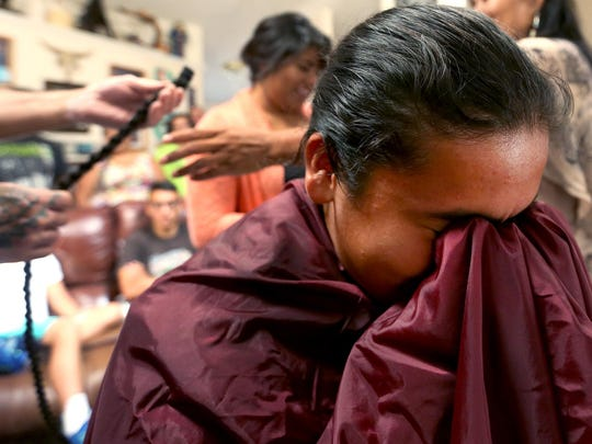 Daniel Tamayo, 13, refuses to look for a few minutes after his braid is cut at his family's home in Monmouth, Ore., on Sunday, Aug. 16, 2015. Tamayo has never cut his nearly three feet of hair before and will be donating it to Locks of Love.