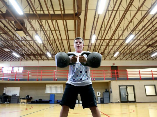 Stuart Heringer, 12, of Salem lifts kettle ball weights during a performance-training class at Courthouse Fitness in Salem.