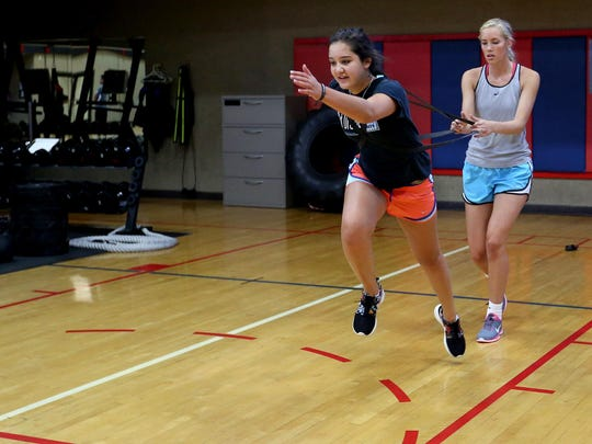 Sarah Stoddard, 16, of Salem runs while being held back for resistance by Reina Strand, 17, of Salem, during a performance training class at Courthouse Fitness.