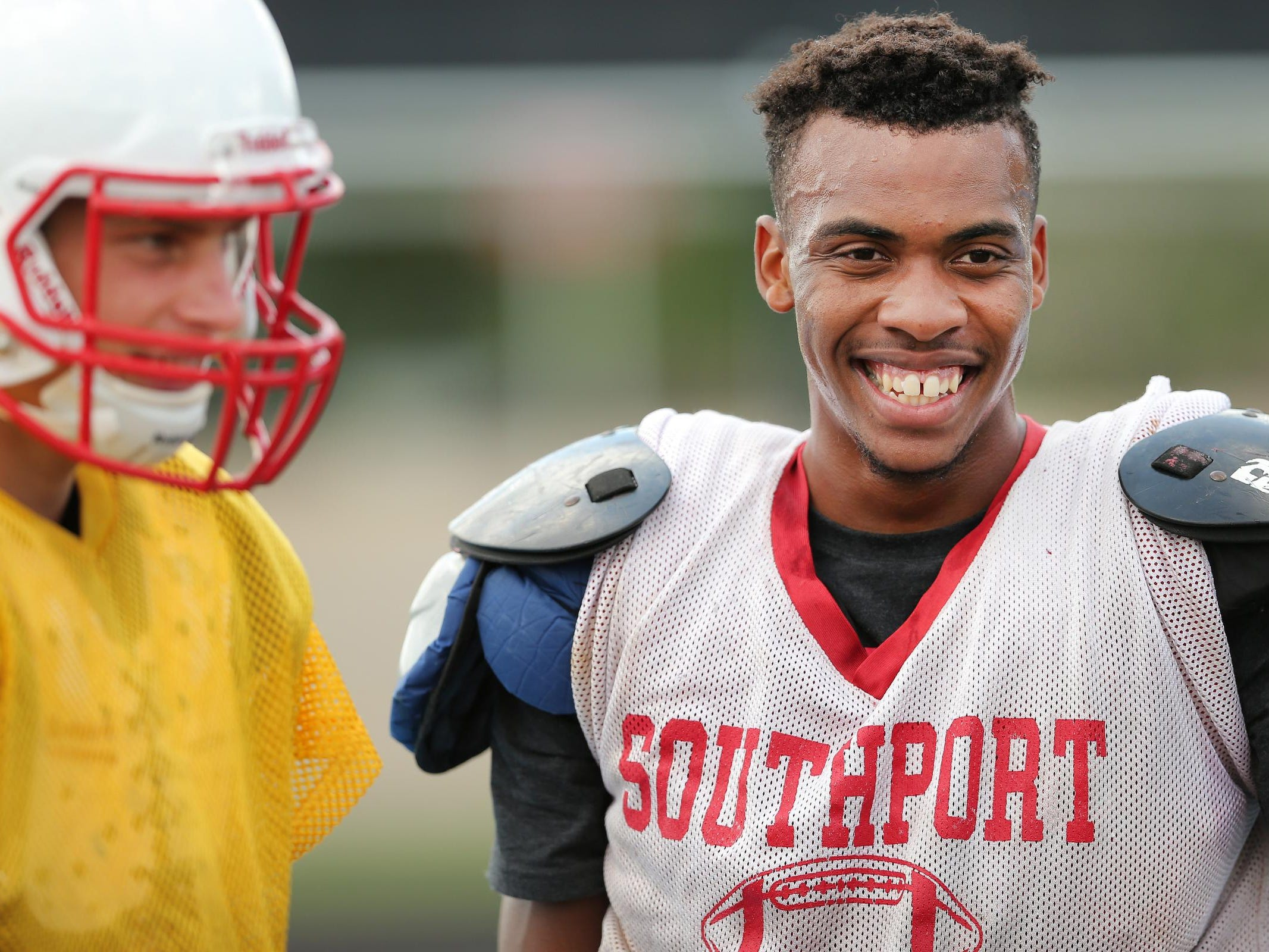 Southport's Paul Scruggs is all smiles while hanging with quarterback Luke Johnston between drills during practice, Aug. 12, 2015.