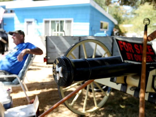 Pete Brusasco displays his homemade Civil War replica cannon in a garage sale during the Dog Daze event in Mill City, on Saturday, Aug. 15, 2015.