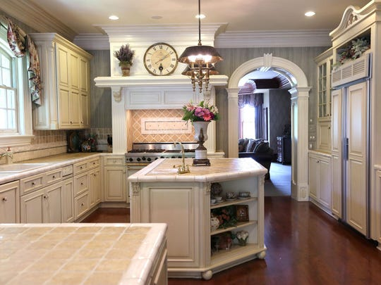 The bright kitchen features lighter wood and a graceful arched entry.