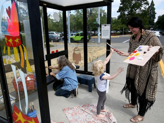 Kristin Blix hands a paintbrush to her son, Blix Norman, 4, while they paint a bus shelter on Summer Street near Marion Street in downtown Salem.