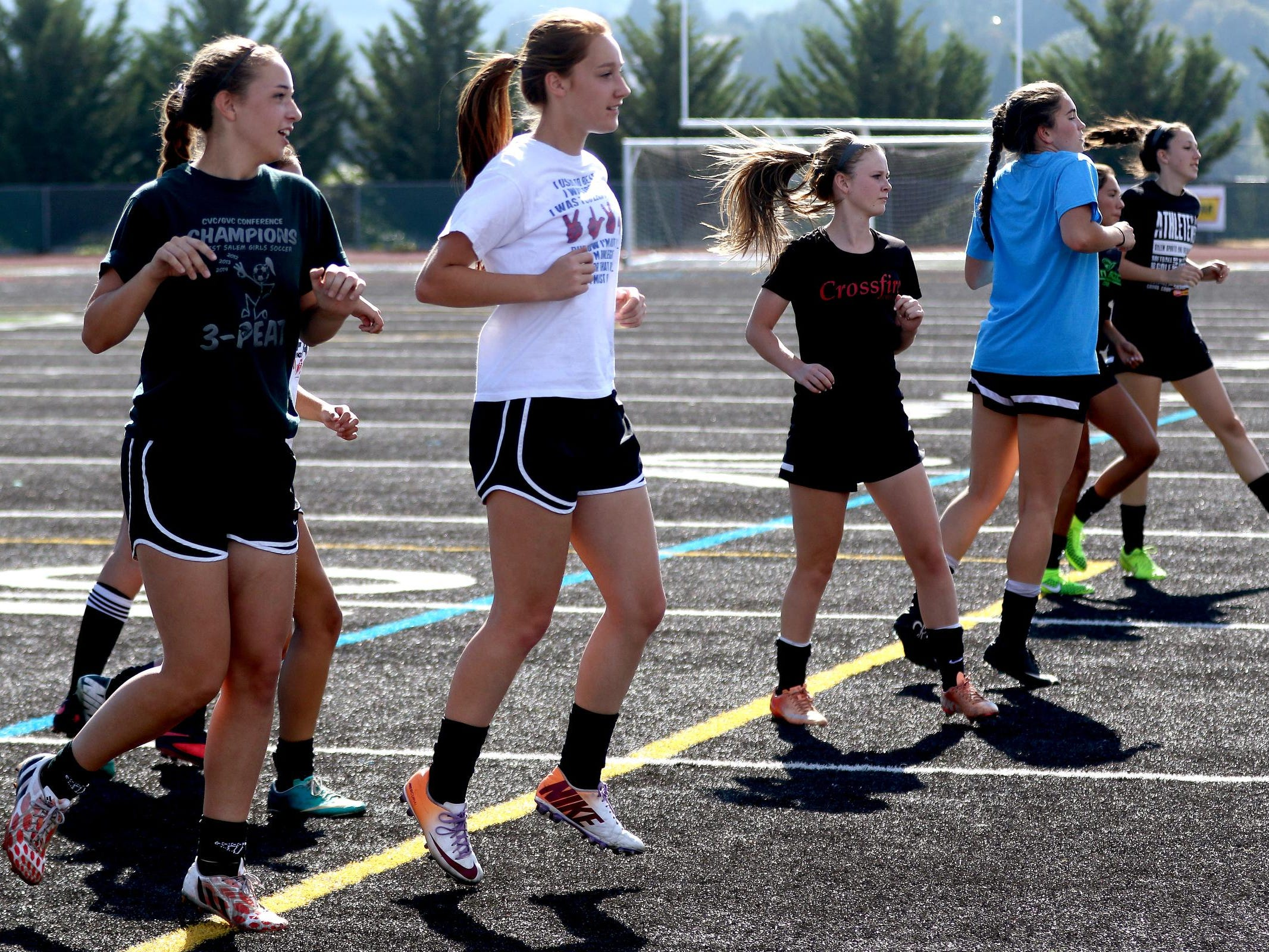 Players warm up during girl's soccer practice at West Salem High School on Thursday, Aug. 27, 2015.