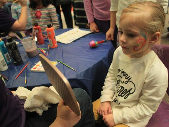 Three-year-old Addison Langseth of North Liberty checks out her face paint during a New Year's celebration at the Iowa Children's Museum on Wednesday, Dec. 31, 2014.