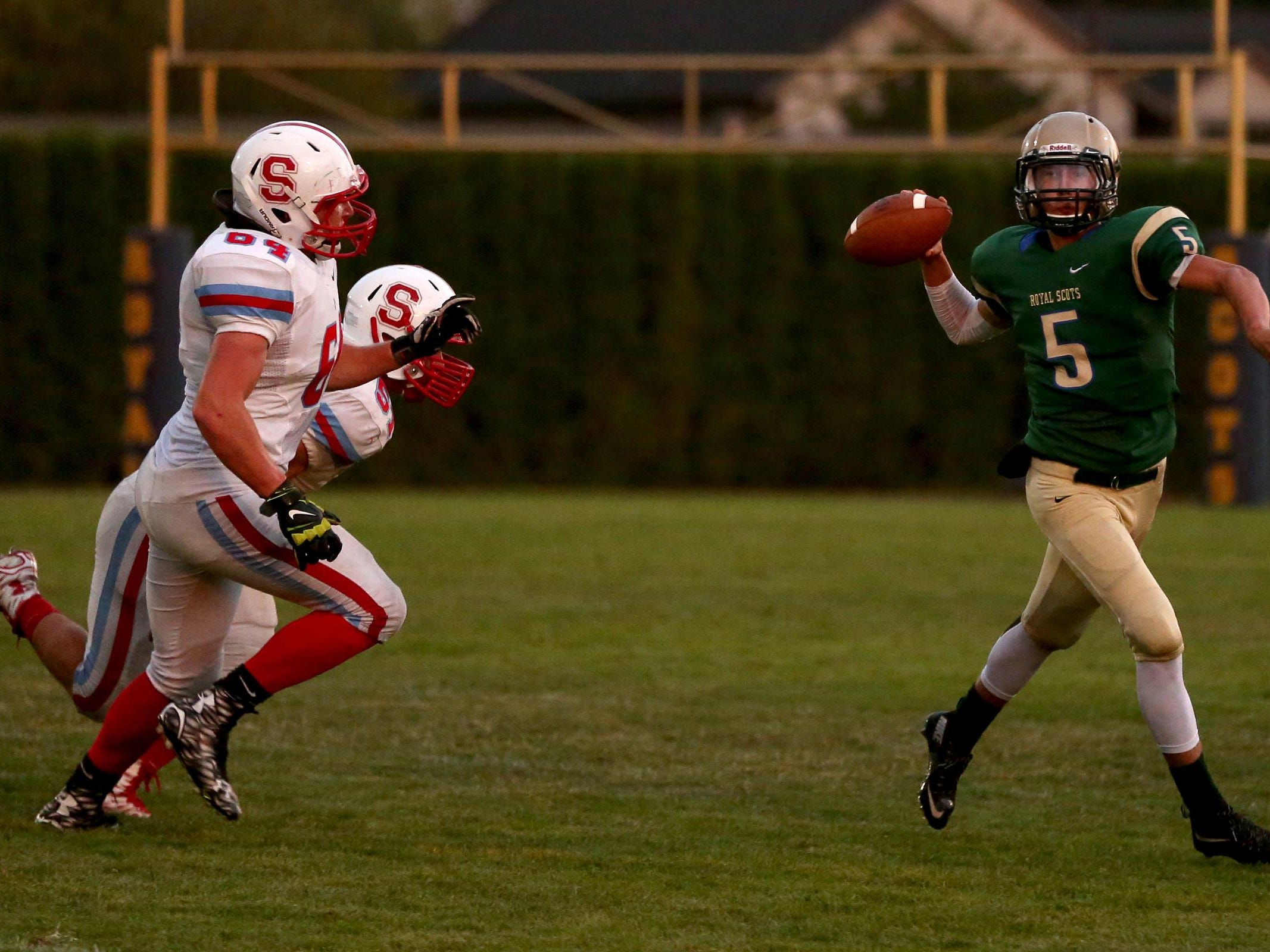 McKay's Matthew Ritchie (5) looks to pass the ball while being chased by South Salem's Justin Peace (64) and Vincent Villarreal (51) in the first half of the South Salem vs. McKay football game at McKay High School in Salem on Friday, Sept. 4, 2015. South Salem leads 26-7 at the half.