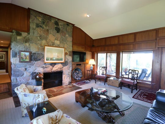 The living room also has a fireplace. It features cherry paneled walls.