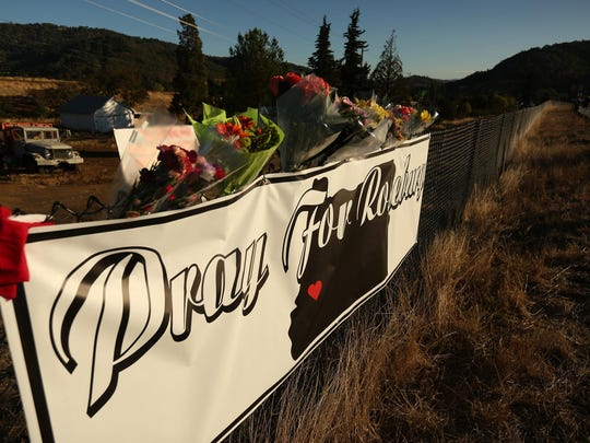 Flowers are placed on a sign near the entrance to Umqua Community College in Roseburg, Ore., on Friday, Oct. 2, 2015. Ten people, including the shooter, were killed and seven others injured in a shooting at Umpqua Community College on Thursday.