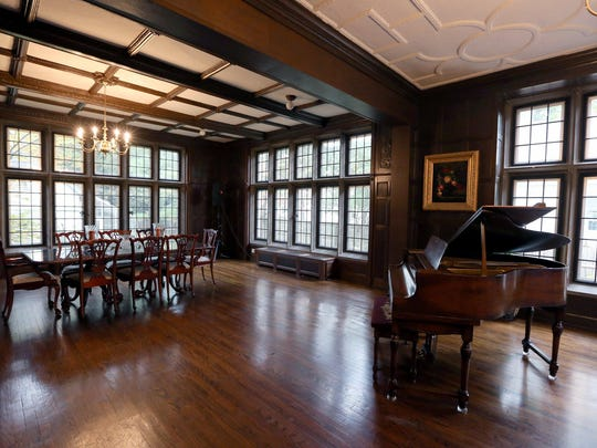 This great room on the first floor is perfect for entertaining. It has wood paneled walls, a limestone fireplace and lots of leaded-glass windows to let in the sunlight or moonlight.