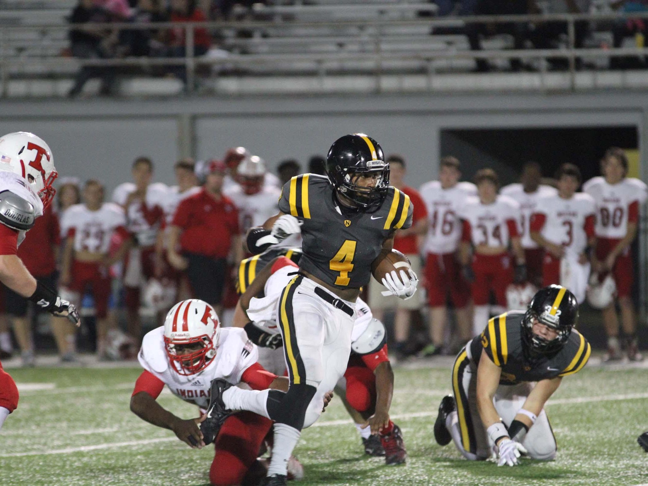 Neville's Donald Jenkins (4) carries the ball for the Tigers against the Tioga Indians Friday night in Monroe.