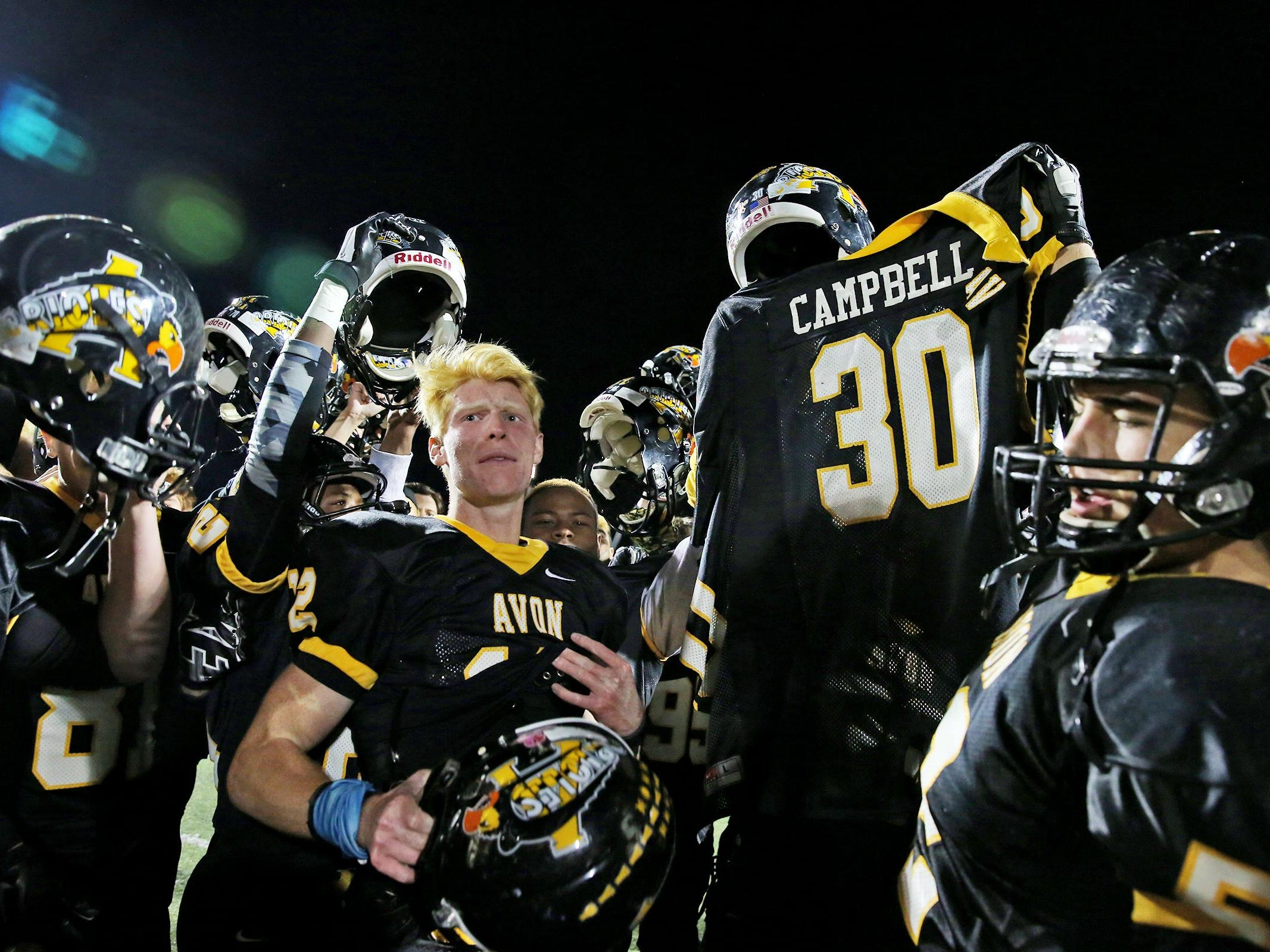 Avon players hold up injured teammate Scott Campbell's jersey as they celebrate the team victory after the Ben Davis at Avon sectional championship, Friday, October 30, 2015. Avon won 27-22. Campbell was injured during the first half and taken off the field by stretcher, then by ambulance to the hospital. Teammates said they won the game for Scott.