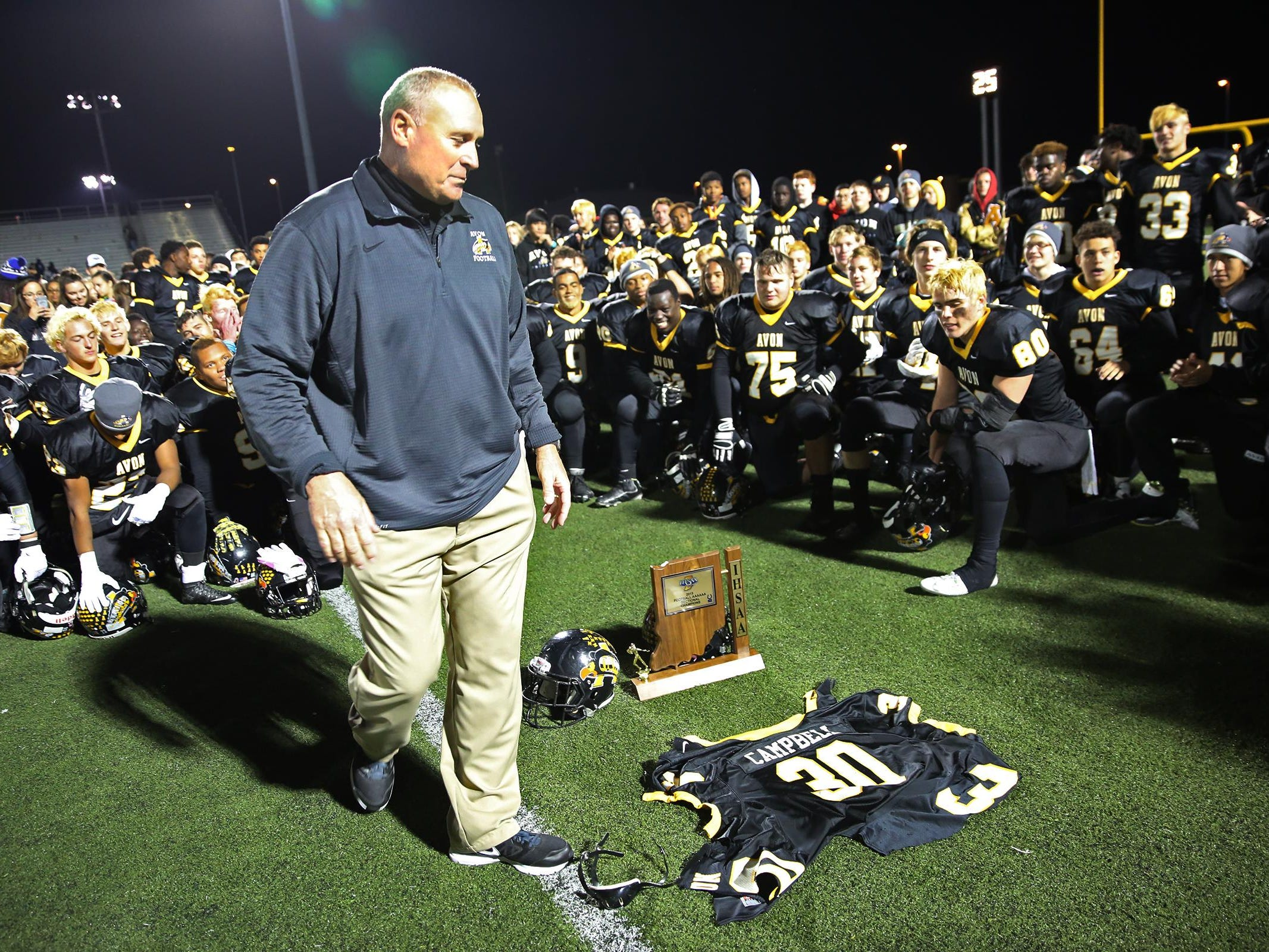 Avon head football coach Mark Bless looks at injured player Scott Campbell's jersey that players held up after the team victory after the Ben Davis at Avon sectional championship, Friday, October 30, 2015. Avon won 27-22. Campbell was injured during the first half and taken off the field by stretcher, then by ambulance to the hospital. Teammates said they won the game for Scott.