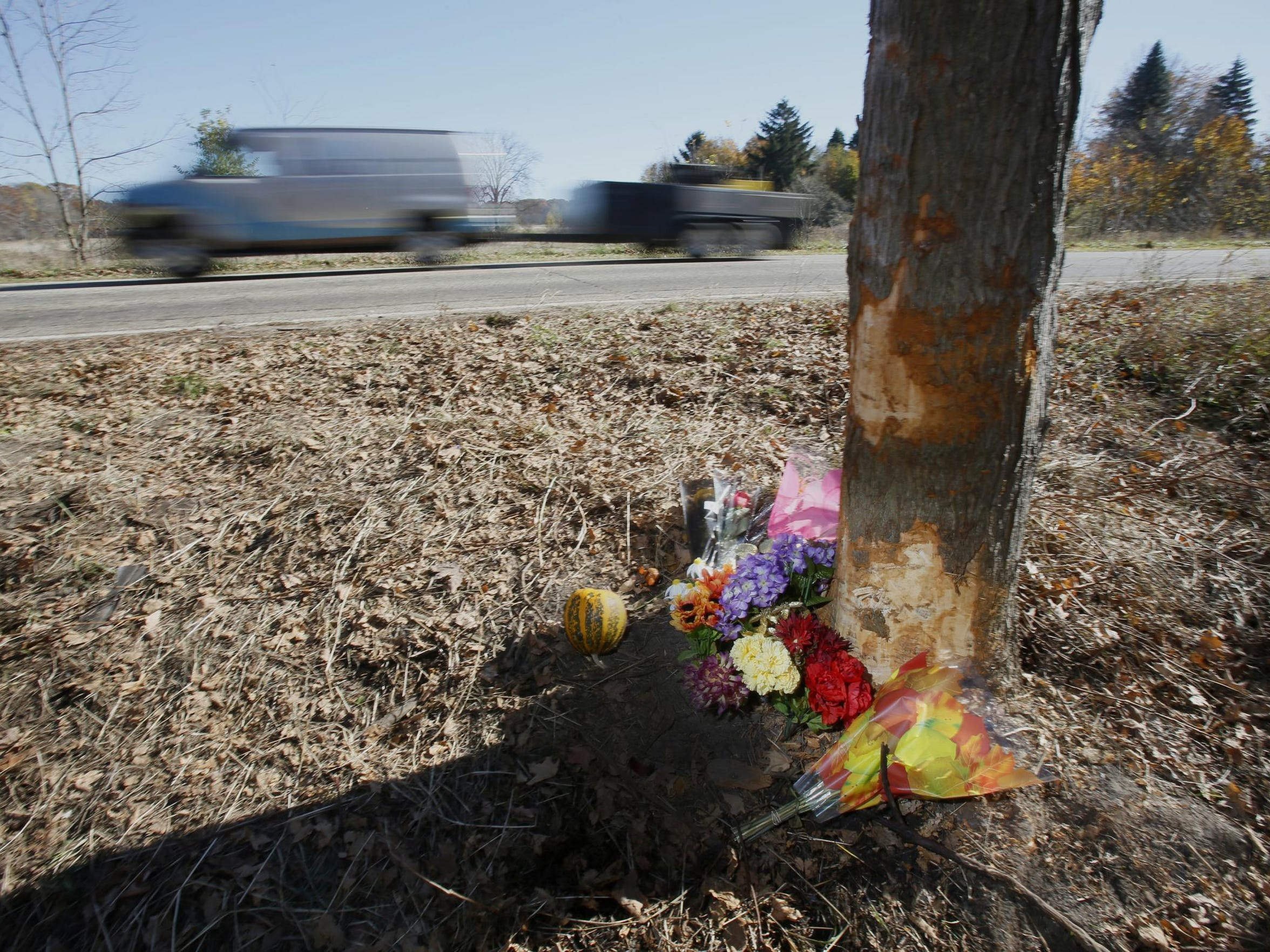 Flowers and other memorials sit against the tree that