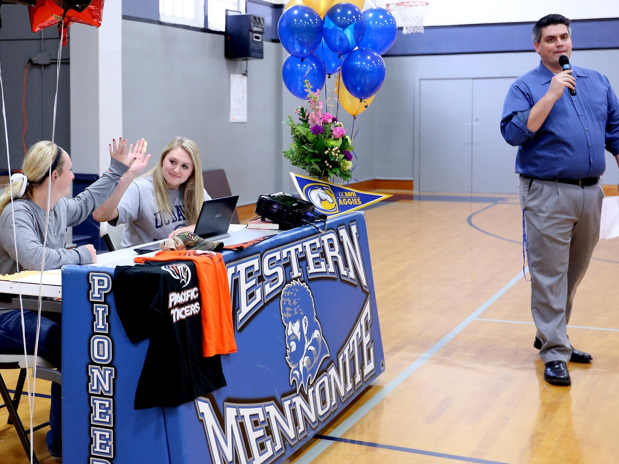 Maddie Hopper and Emma Gibb, center, high five while girl's basketball coach Robby Gilliam introduces them before they sign letters of intent to play softball with the University of the Pacific and basketball at UC Davis, respectively, at Western Mennonite High School in Salem on Wednesday, Nov. 11, 2015.