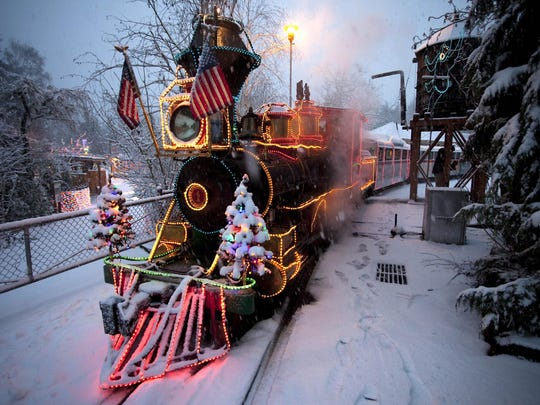 The zoo train makes its first run during a previous Zoolights in a snowstorm at the Oregon Zoo.
