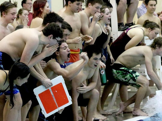Swimmers cheer on their teammates while keeping track of laps completed in the West Salem vs. South Salem swim meet at the Kroc Community Center in Keizer on Tuesday, Jan. 5, 2016.