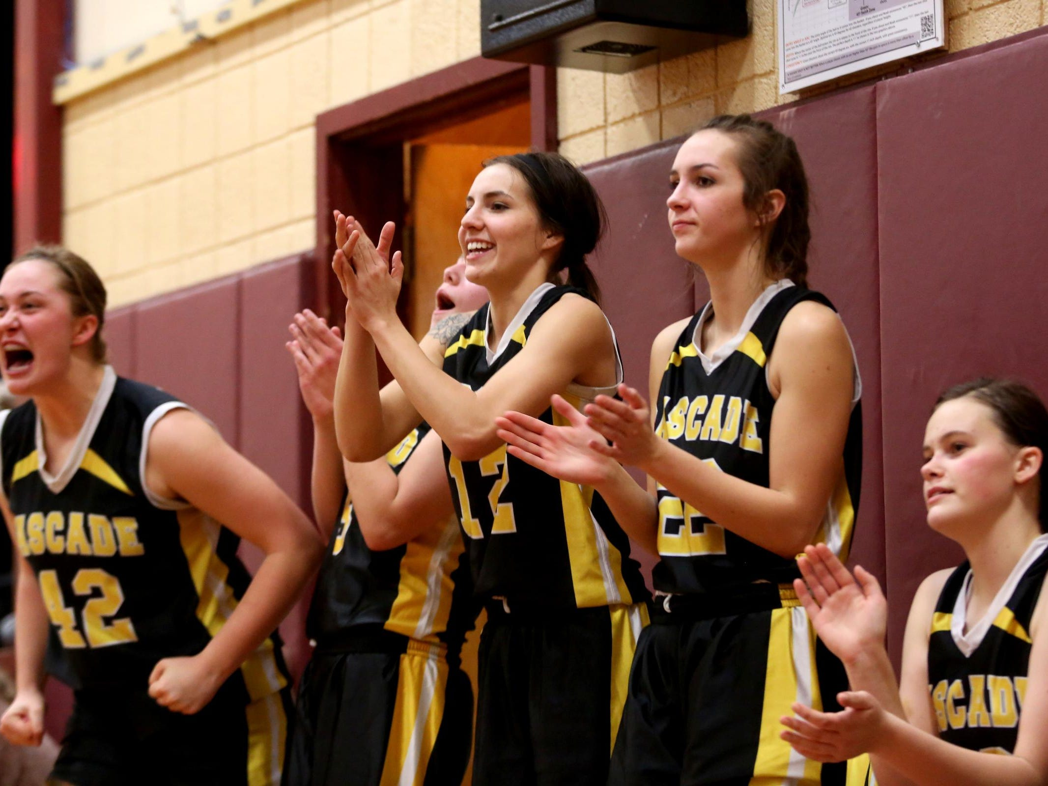 The Cascade bench celebrates a play in the Cascade vs. Junction City girl's basketball game at Junction City High School on Tuesday, Jan. 12, 2015. Cascade won the game 61-43.