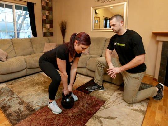 Health columnist Kyle Davey coaches his wife Ana on a kettle bell deadlift.