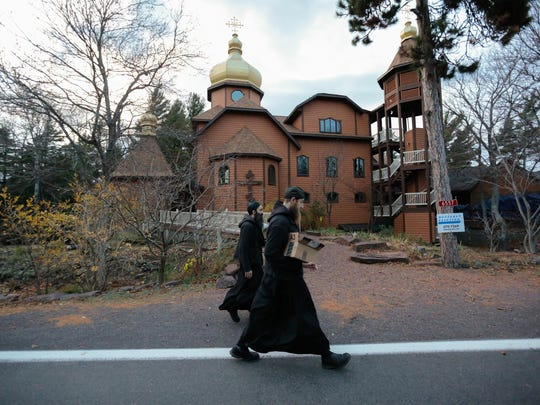 Father Ephrem, foreground, and Father Ambrose return to the Holy Transfiguration Skete monastery in Eagle Harbor in November after working in the bakery of the Jampot before evening prayer in the Upper Peninsula.