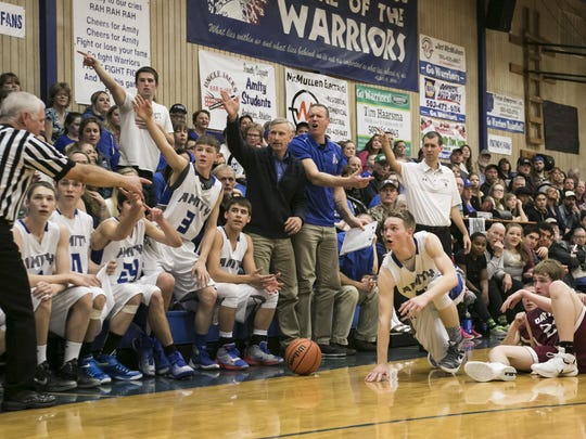 Amity players, fans and coaches look to the referee for a ruling at a game at Amity High School on Friday, Jan. 29, 2016. Amity won 81-58.