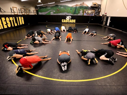 Wrestlers stretch before practice at Cascade High School in Turner onTuesday.
