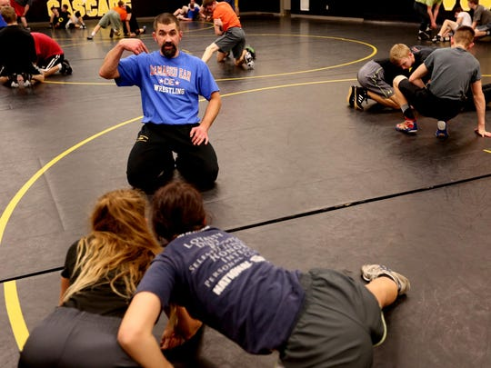 Head Coach Jason Lovell gives technique instructions to wrestlers Brooklynn Peterson and Morgan Zehner during practice at Cascade High School.