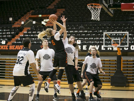 Oregon State senior Jamie Weisner (15) goes up for a basket as Oregon State student Derek Saling attempts to block the shot during a co-ed scrimmage on Thursday, Feb. 10, 2016. A small group of male OSU students, called Tune Squad, scrimmage with the women's basketball team roughly two to three times a week to give the team more practice against opponents that may be bigger or stronger than their regular opponents.