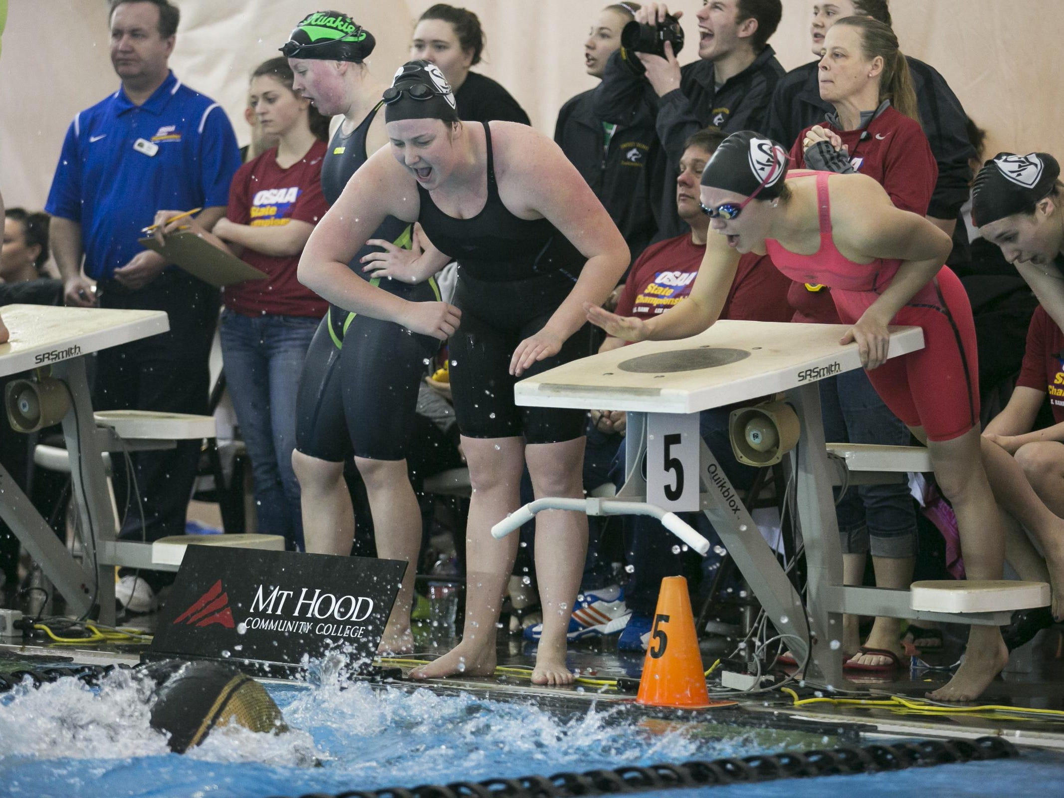 Kiera Supple (left) and Emma Boles (right) cheer as teammate Callie Hinson swims the girls 400 yard free relay for Salem Academy at the OSAA Swimming State Championships at Mount Hood Community College on Saturday, Feb. 20, 2016.