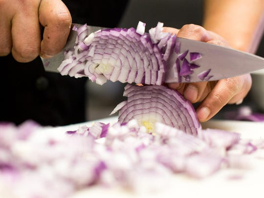 Smith dices onions for Matar Paneer. Starting in the spring, Masala will source as many ingredients as possible from around the Missoula valley.