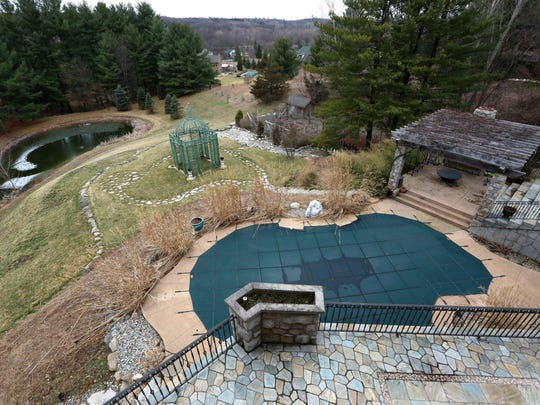 Hilly grounds, with a pool and pond, allow room to roam. The house sits on 4.5 acres.