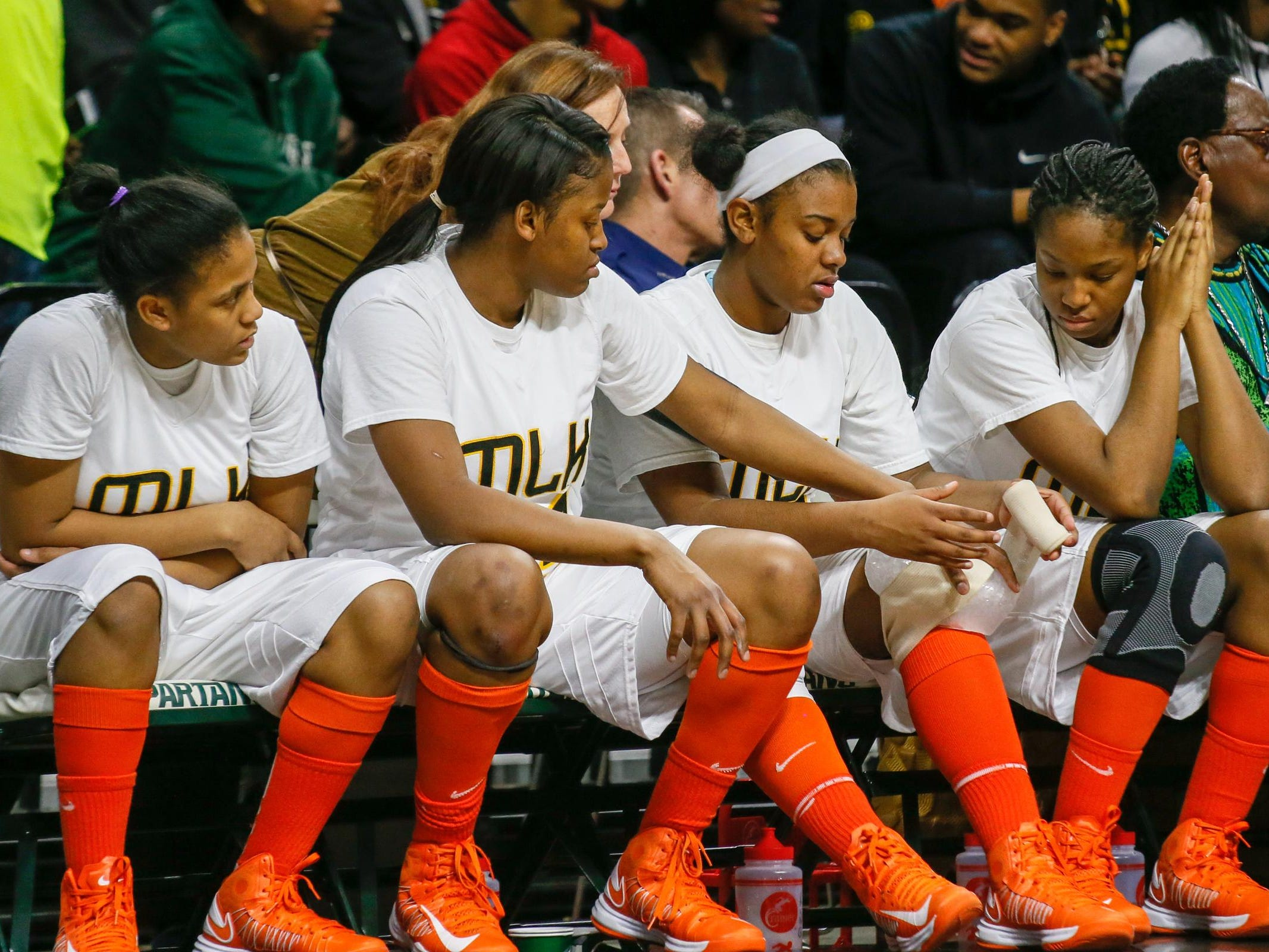 Detroit King's Jordan Lewis ices her knee in the fourth quarter Friday. The team's orange socks and shoes are a throwback to when the school was Detroit Eastern.