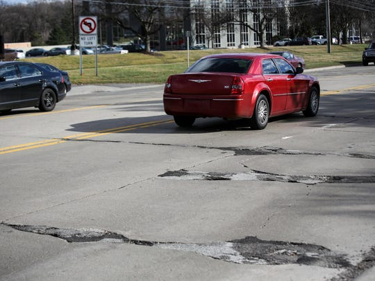 Potholes can be seen along Lahser road near Civc Center Drive in Southfield on Thursday, March 17, 2016.