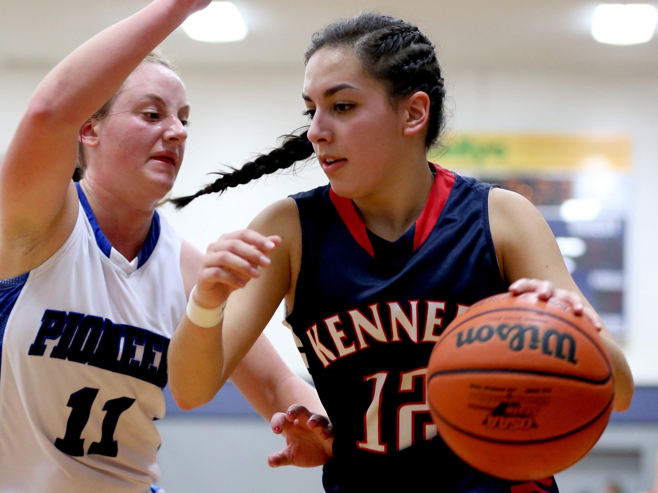 Kennedy's Lakin Susee (12) drives past Western Mennonite's Maddie Hopper (11) in the second half of the Kennedy vs. Western Mennonite girl's basketball game at Western Mennonite High School in Salem on Wednesday, Dec. 16, 2015. Kennedy won the game 44-41.