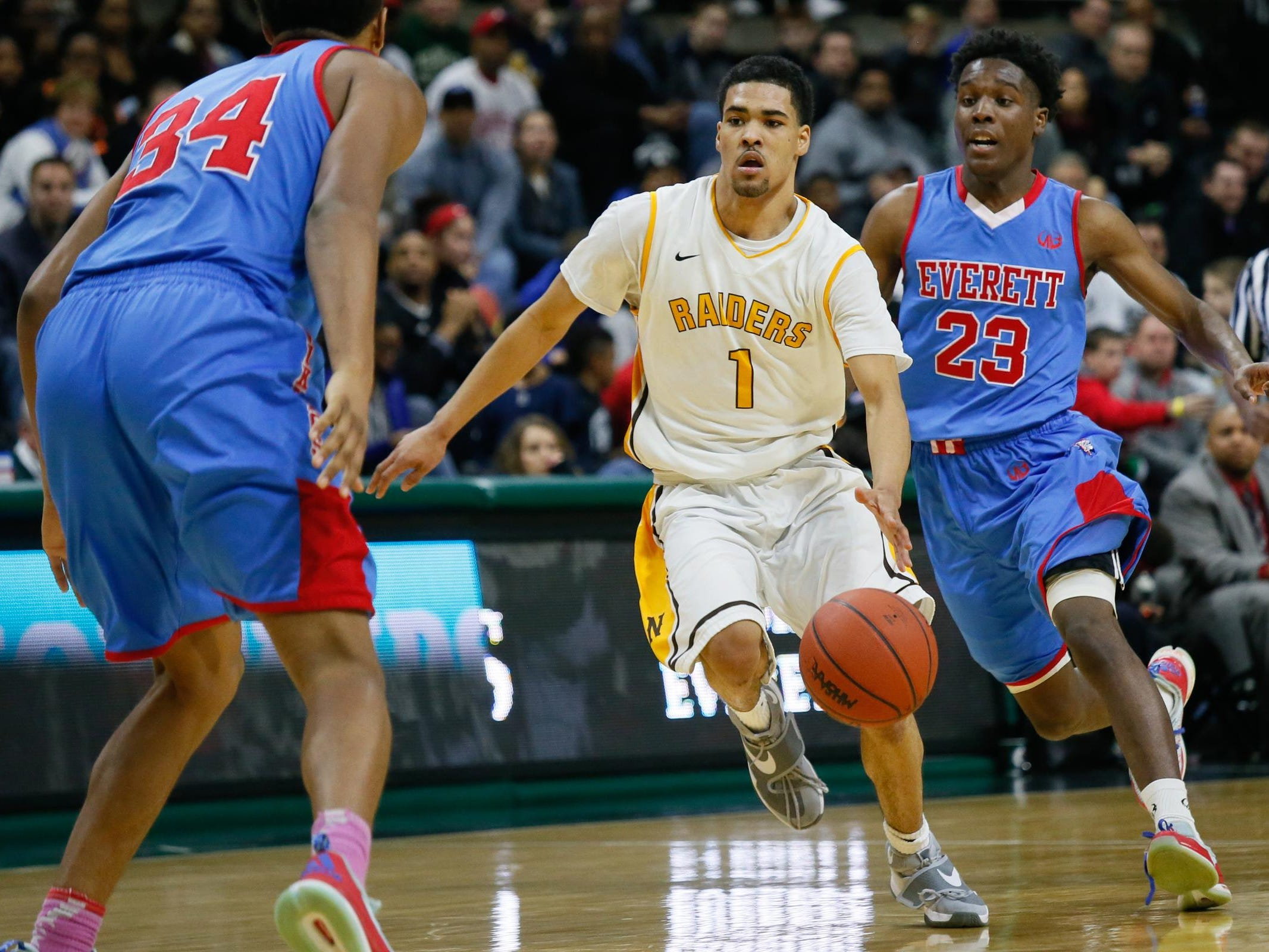 North Farmington's Billy Thomas has a fast break against Lansing Everett's Victor Edwards and Diego Robinson, during the MHSAA boys basketball Class A semifinals at the Breslin Center in East Lansing, Mich. on Friday, March 25, 2016.