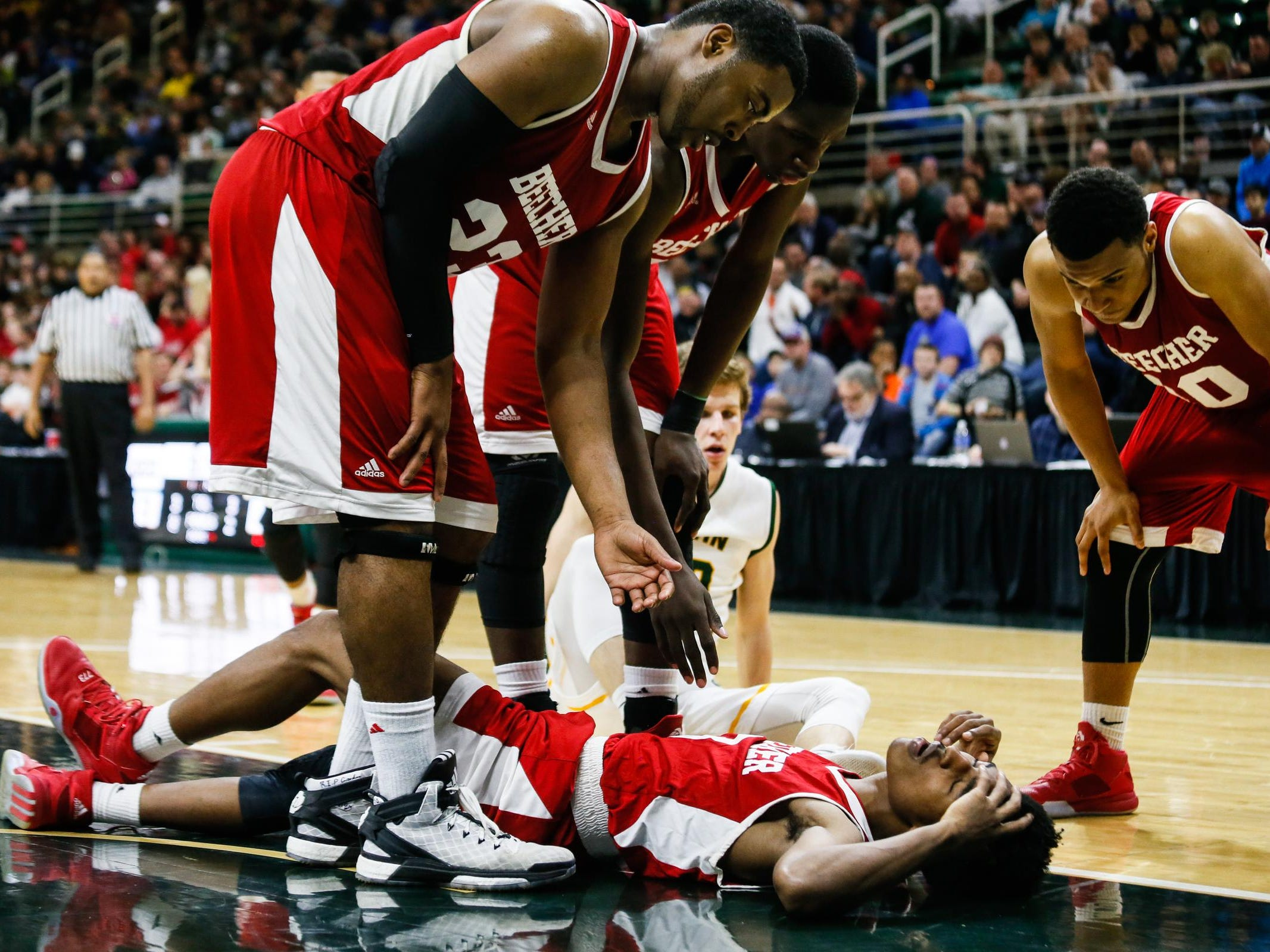 Flint Beecher's Jordan Roland lies on the floor after being fouled hard by Grandville Calvin Christian during the Class C state title game.