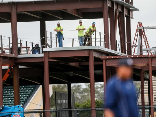Construction workers take a break by watching Tigers spring training at Joker Marchant Stadium in Lakeland, Fla.