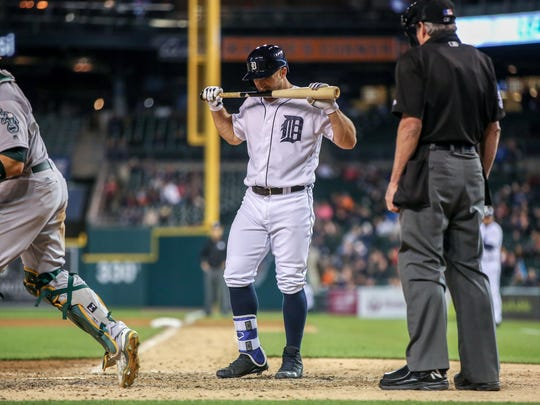 Tyler Collins bites his bat after fanning in the eighth inning Monday at Comerica Park. Two innings earlier, Collins was booed after a misplay and promptly flipped off the fans.