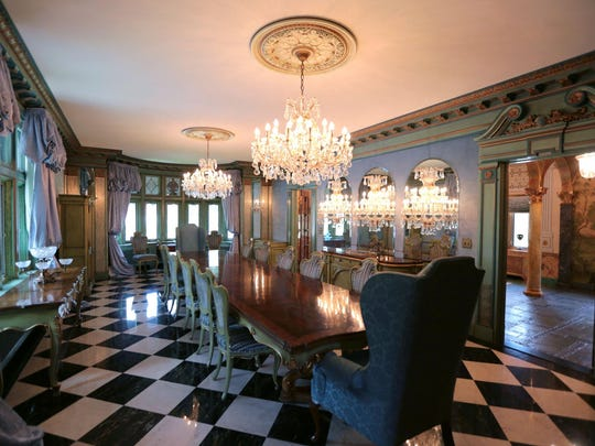 The dining room has marble on the floor, velvet and crystal on walls and two chandeliers.