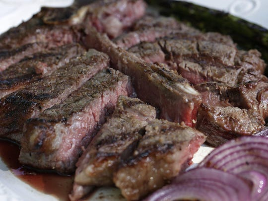 Reverse-sear New York Steaks with Red Wine Butter. Grilling and cutting steak to serve Monday May 29, 2016. Mandi Wright/Detroit Free Press