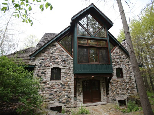 The front of the home, which is built of stone and has a wood shingle roof.