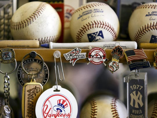 Pins and other Volcanoes memorabilia sit among a large collection of baseball items in OK Barber Shop, owned by avid baseball fan Mike Witenberger.