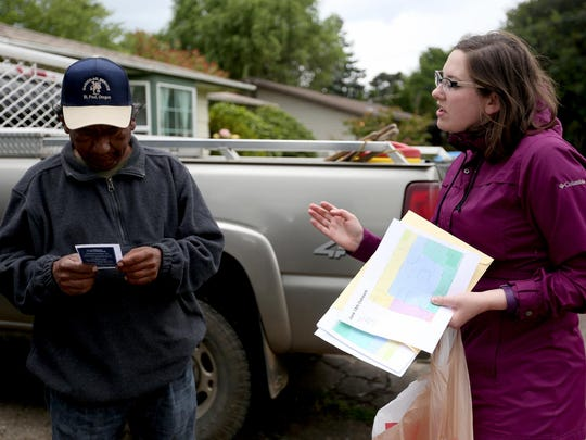 Kirsten Straus, the community cat coordinator with the Willamette Humane Society, gives Fernando Tamanaja information about a free spay and neuter program for cats in the 97301 zip code in Salem on Saturday, June 18, 2016.