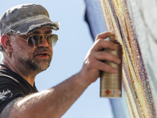 Detroit artist Fel3000ft works on a section of a 100ft-by-20ft mural at Buddy's Pizza in Detroit on Thursday July 14, 2016 that incorporates the spirit of Detroit holding the company's original square pizza they are having done as part of their 70th anniversary of the family owned-restaurant.