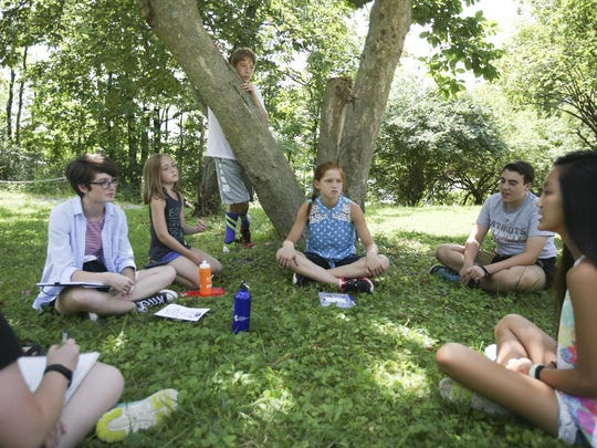 """The """"Skittles Taste the Rainbow"""" team collaborates on an idea for a project during Climate Camp at the Peace Learning Center at Eagle Creek Park on July 25, 2016."""