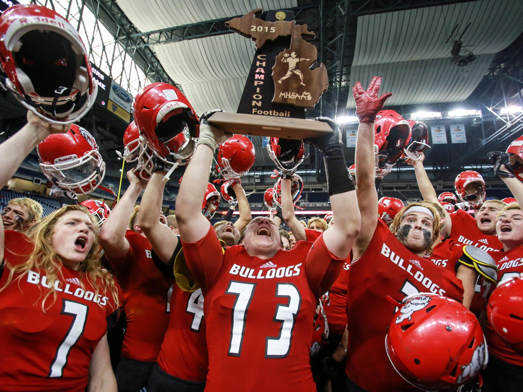 Romeo Christopher Zanke lifts the MHSAA Football Champion trophy in the air surrounded by his teammates, after defeating Detroit Cass Tech in the Michigan High School Athletic Association football Division 1 finals at Ford Field in Detroit on Saturday, Nov. 28, 2015.
