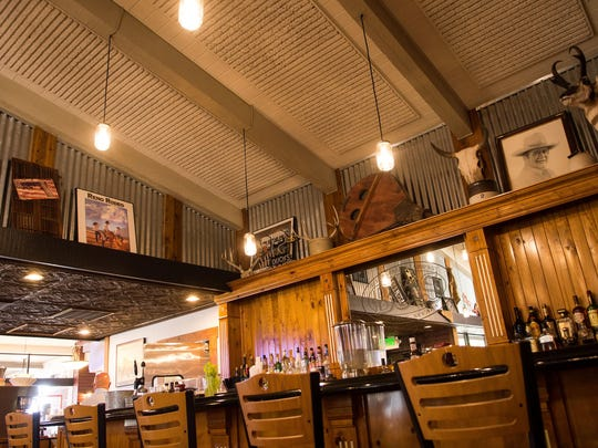 The columns on the knotty pine bar at the back of BJ's Barbecue are inset with silver leaf. The bellows above, the corrugated panels and other elements are in keeping with the restaurant's stylish rusticity.