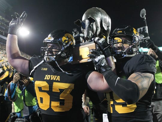 Iowa's Austin Blythe, left, and Melvin Spears carry the Floyd of Rosedale trophy on Nov. 14, 2015, after defeating Minnesota 40-35 in Iowa City.